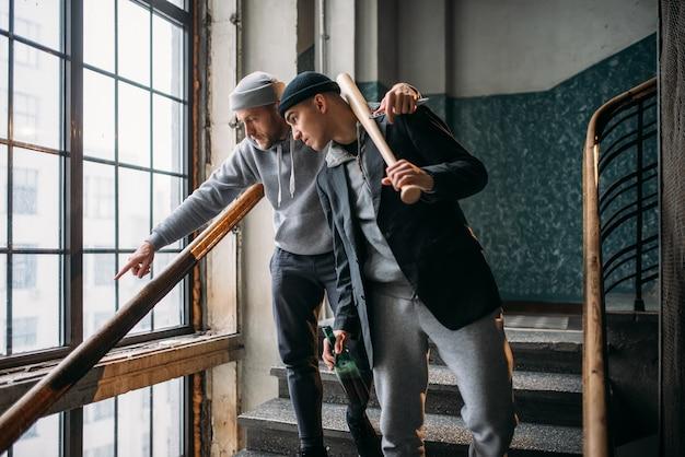 Dos ladrones callejeros con bate de béisbol esperando a la víctima. criminal, peligro de robo, tipos peligrosos