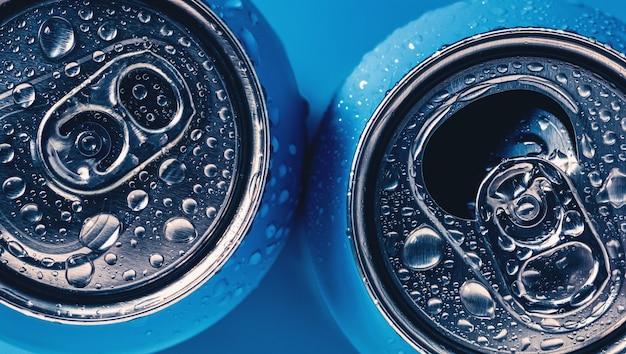 Dos latas de bebida energética de aluminio sobre fondo azul con gotas de agua