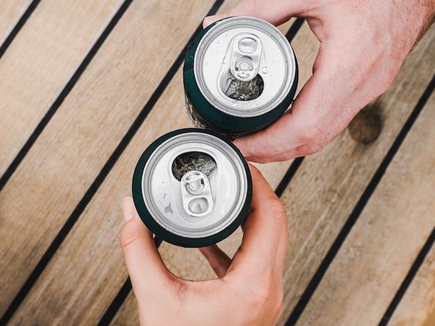 Dos latas de cerveza, manos femeninas y masculinas.