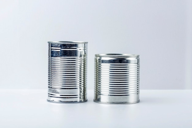 Dos latas (conservas) sobre fondo blanco. suministros de alimentos durante la cuarentena de coronavirus y el autoaislamiento. entrega de comida, donación, apoyo voluntario.