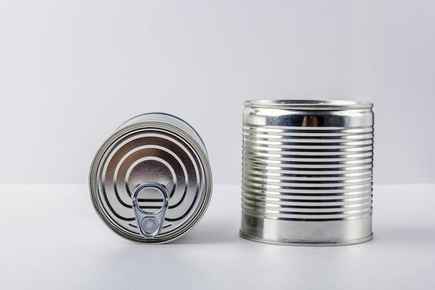 Dos latas sobre fondo blanco. suministros de alimentos durante la cuarentena de coronavirus y el autoaislamiento. entrega de comida, donación, apoyo voluntario.