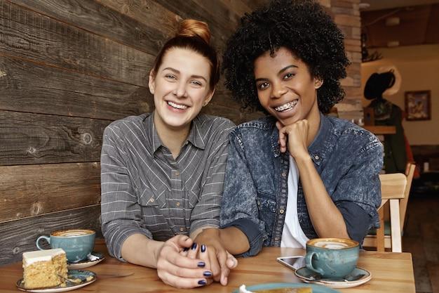 Dos lesbianas de diferentes razas pasando un buen rato juntos en la cafetería.