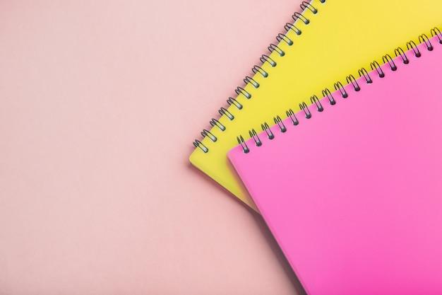 Dos libretas de color rosa y amarillo sobre un fondo rosa.
