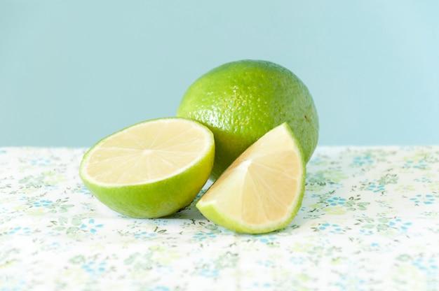 Dos limones verdes frescos (uno en trozos) sobre una mesa con un mantel de flores y un fondo celeste.