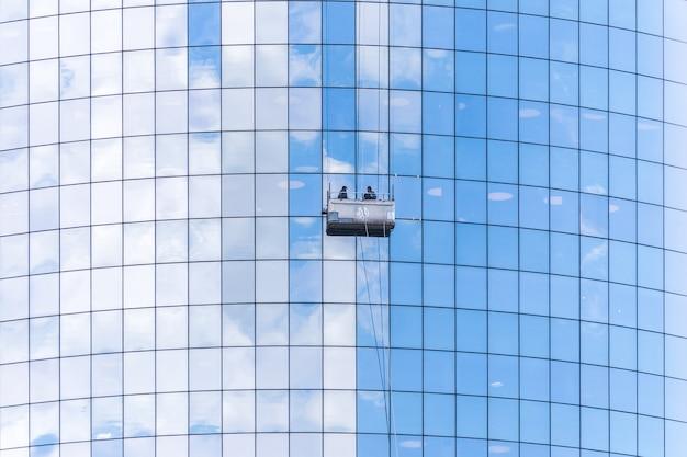 Dos limpiadores que lavan las ventanas de los rascacielos modernos