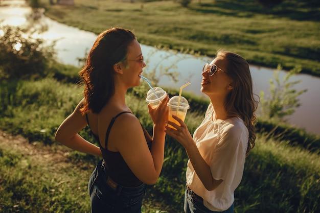Dos lindas amigas beben cócteles, vestidas con una camiseta en blanco y negro, divirtiéndose en el verano, al atardecer, expresión facial positiva, al aire libre