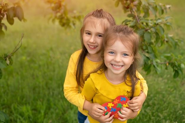 Dos lindas chicas divertidas sostienen un corazón hecho de papel con rompecabezas dentro