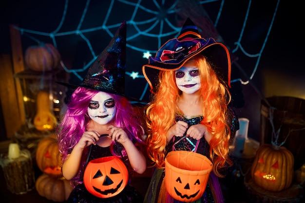 Dos lindas hermanas divertidas celebran la fiesta. niños alegres en trajes de carnaval listos para halloween.
