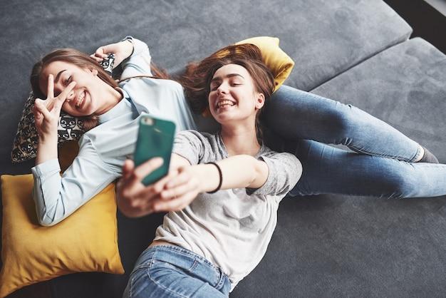Dos lindas hermanas gemelas sonrientes sosteniendo smartphone y haciendo selfie.