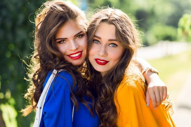 Dos lindas mujeres abrazándose y sonriendo