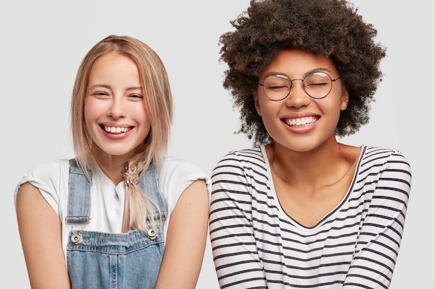 Dos lindas mujeres diversas se ríen positivamente, tienen amplias sonrisas, escuchan anécdotas divertidas de un amigo, pasan tiempo libre juntas después de tener clases, expresan felicidad, aisladas sobre una pared blanca