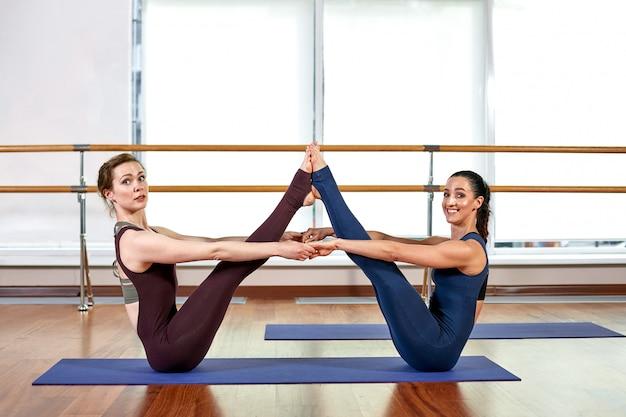 Dos lindas mujeres jóvenes delgadas están haciendo la pose de yoga mientras están de pie en un gimnasio brillante cerca de una ventana grande.