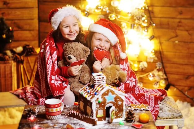 Dos lindas niñas divertidas con sombreros rojos de papá noel cubiertos con una sonrisa a cuadros, decoración navideña y luces y hacen una hermosa casa de pan de jengibre