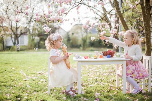 Dos lindas niñas rubias de 3 años están jugando en el parque cerca de una magnolia en flor. beber té. pascua de resurrección. primavera.