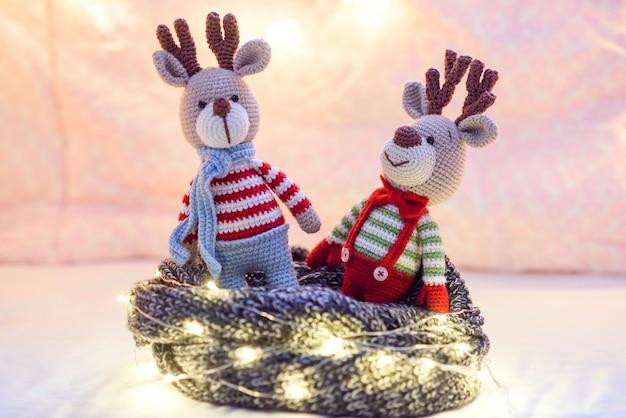 Dos lindos ciervos de vacaciones en suéteres a rayas con luces de navidad en el rosa.