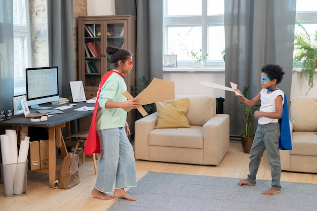 Dos lindos hermanos de raza mixta en disfraces de superhéroes que se divierten en el suelo mientras juegan con espadas de cartón en la alfombra de la sala de estar