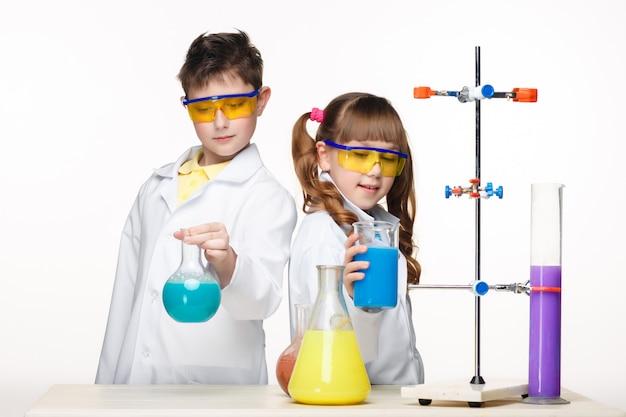 Dos lindos niños en clase de química haciendo experimentos