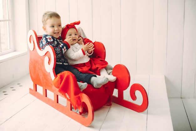 Dos lindos niños sentados en una decoración navideña