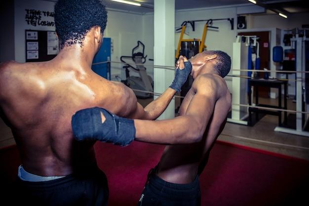 Dos luchadores afroamericanos practicando técnicas de derribo de mma en el ring.