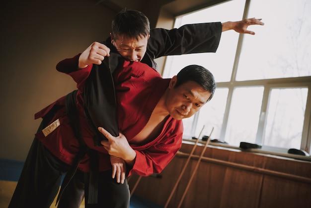 Dos luchadores de artes marciales en kimono negro y rojo.