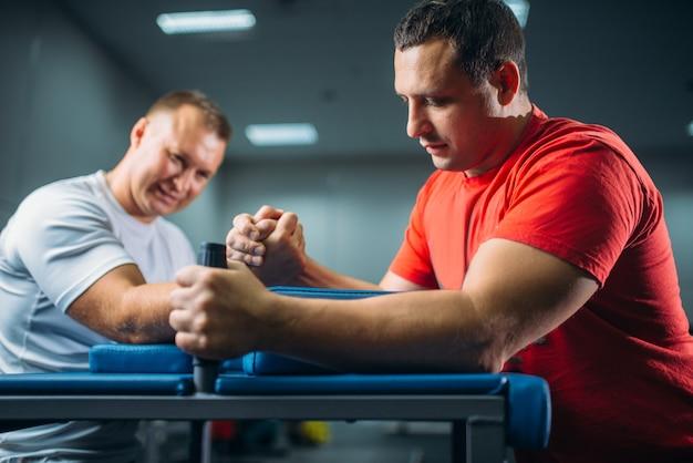Dos luchadores de brazos peleando en sus manos en la mesa con alfileres, batalla en acción, competencia de lucha libre.