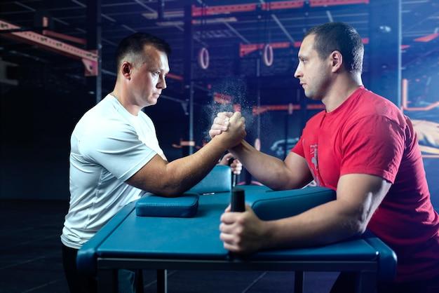 Dos luchadores de brazos en posición inicial, competencia de lucha libre. desafío de lucha, deporte de potencia
