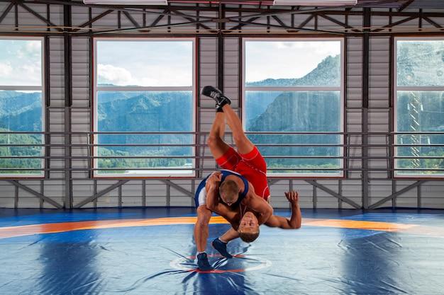 Dos luchadores grecorromanos en ropa deportiva hacen un tiro a través del cofre en una alfombra de lucha en el gimnasio