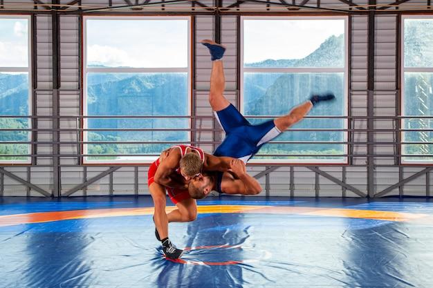 Dos luchadores grecorromanos en uniforme rojo y azul haciendo un muslo tirar sobre una alfombra de lucha en el gimnasio.