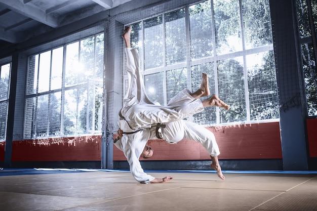 Dos luchadores de judo que muestran habilidad técnica mientras practican artes marciales en un club de lucha