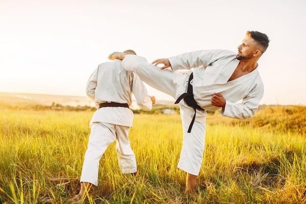 Dos luchadores de karate, patada en el estómago