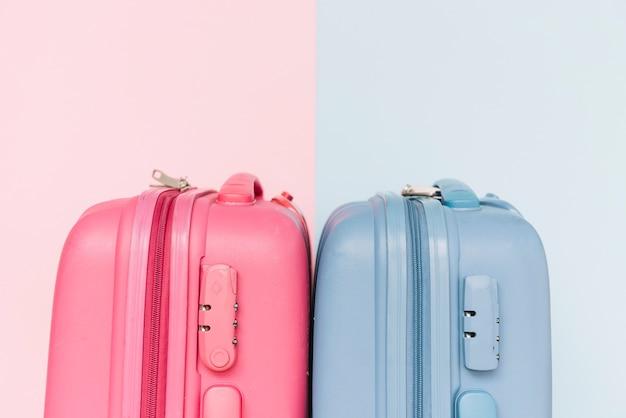 Dos maletas de equipaje de plástico azul y rosa sobre fondo dual