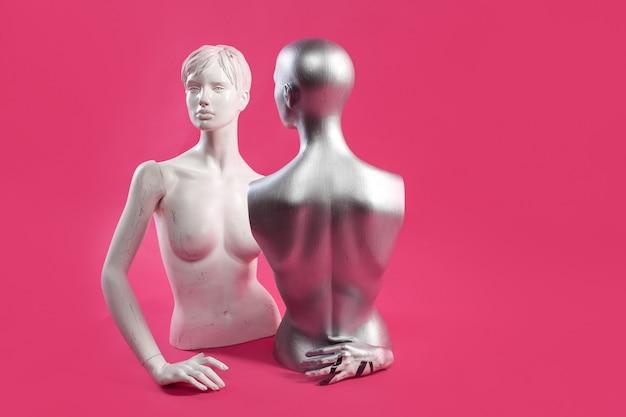 Dos maniquíes en una pared rosa. moda y diseño.