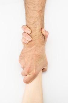 Dos manos se ayudan en un fondo blanco. las personas se ayudan mutuamente. asistencia mutua, ayuda en una situación difícil.