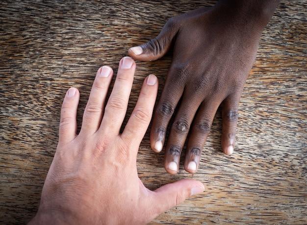 Dos manos blancas y negras haciendo equipo juntos