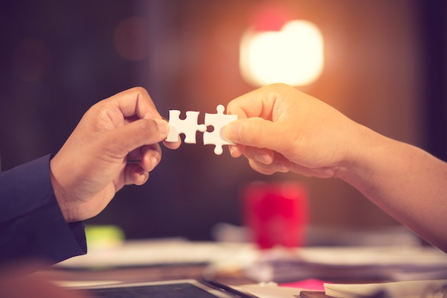 Dos manos de empresario para conectar pieza de puzzle.