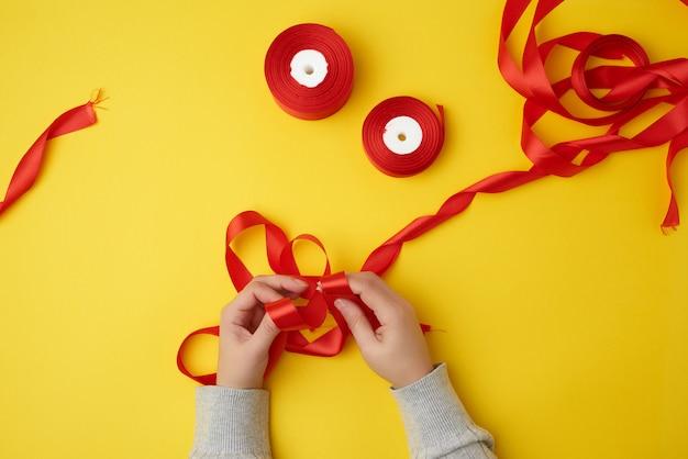 Dos manos femeninas atan un lazo con una cinta roja y carretes con una cinta de raso