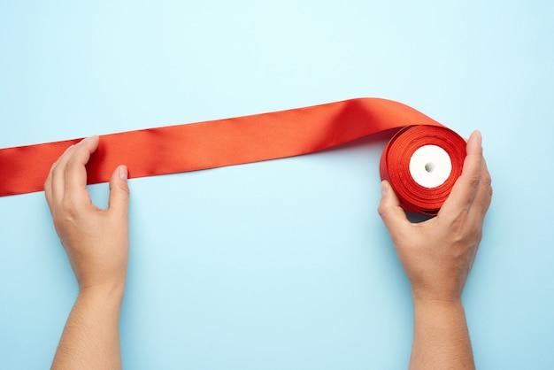 Dos manos femeninas y cintas de seda roja sobre un azul