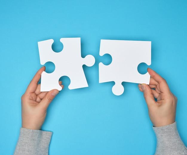 Dos manos femeninas que sostienen grandes rompecabezas blancos de papel blanco