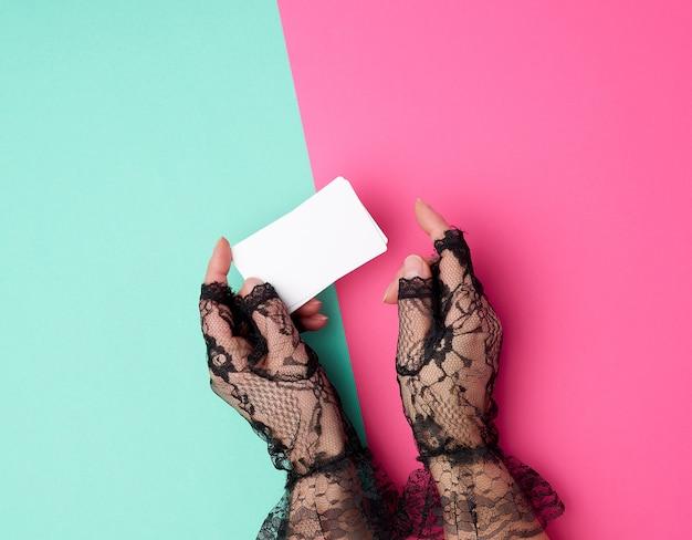 Dos manos femeninas que sostienen una pila de tarjetas de visita vacías del libro blanco