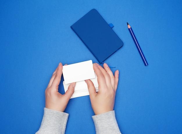 Dos manos femeninas sosteniendo una pila de tarjetas de visita de papel blanco vacías sobre un fondo azul.