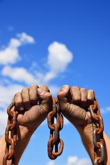 Dos manos de hombre en el barro sostienen una cadena de metal oxidado.
