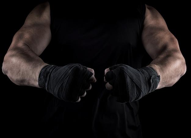 Dos manos de hombre envueltas en un vendaje negro, partes del cuerpo delante del torso