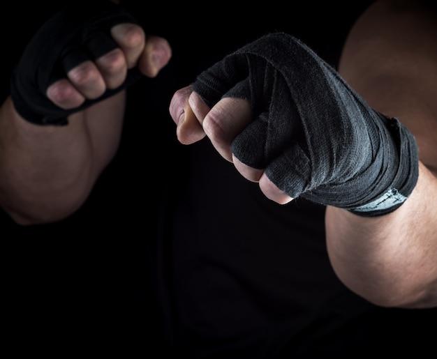 Dos manos de hombre rebobinadas con una banda textil negra.