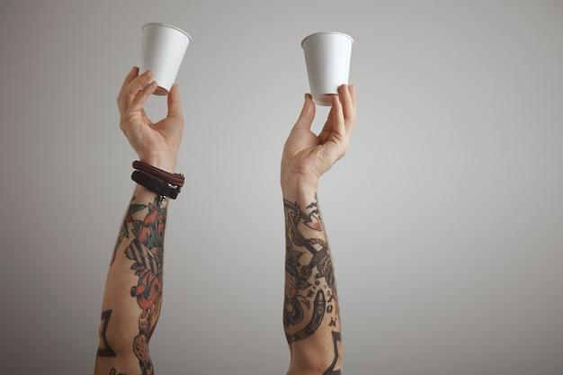 Dos manos de hombres tatuados brutales sostienen papel en blanco para llevar vidrio de cartón en el aire. presentación aislada en blanco.