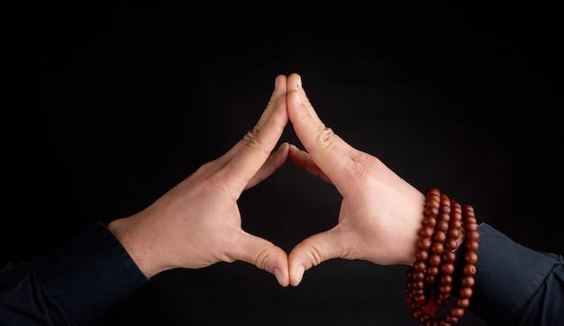 Dos manos masculinas conectadas sobre un fondo negro