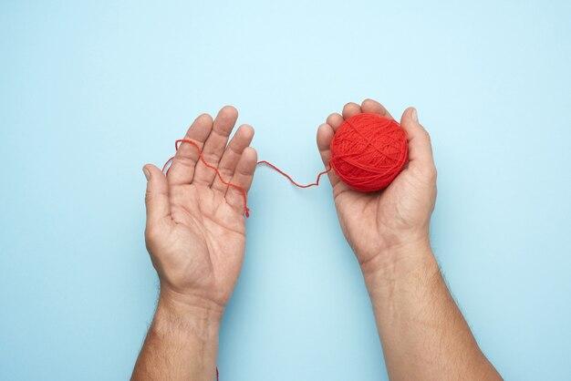 Dos manos masculinas sostienen una bola de hilos de lana roja