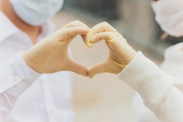 Dos manos de una pareja en guantes de plástico abrazados.