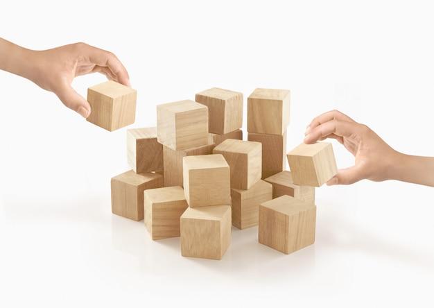 Dos manos que juegan la caja de madera en aislado.