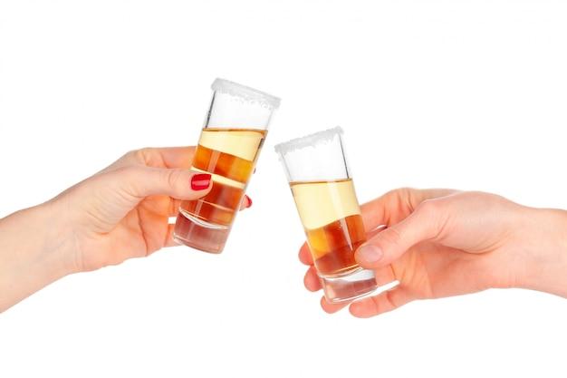 Dos manos que tintinean los vidrios con el cóctel del tiro aislado en blanco