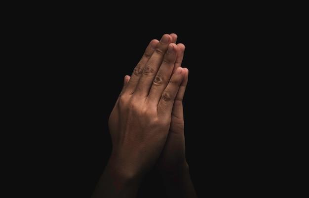 Dos manos rezando rinden respeto sobre fondo oscuro, esta acción para el concepto de cultura de tailandia.